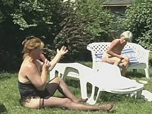 Bejaarde lesbo dames genieten van dildo sex in de tuin